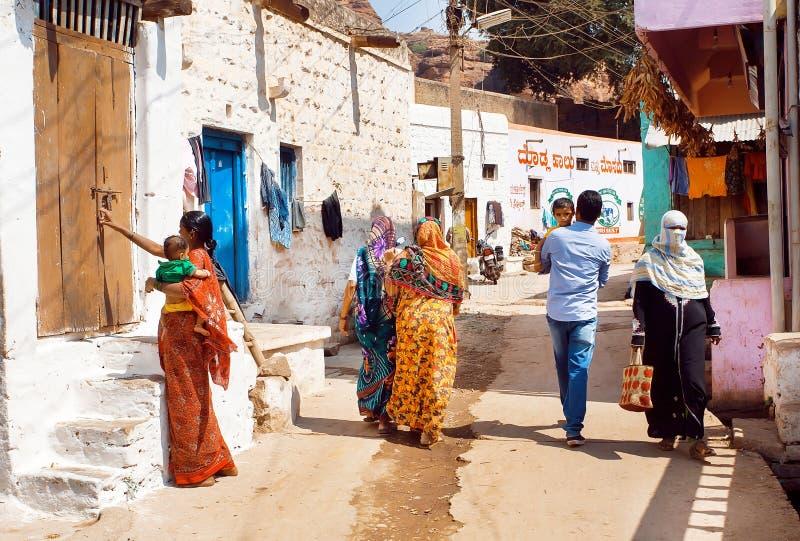 Mucha gente en la calle estrecha con las casas rurales del ladrillo de la pequeña ciudad en el estado de Karnataka fotos de archivo