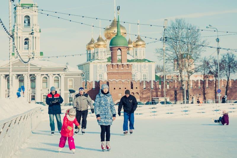 Mucha gente en la pista de patinaje de la ciudad en el cuadrado central en el fondo de Tula Kremlin fotos de archivo libres de regalías