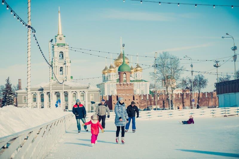 Mucha gente en la pista de patinaje de la ciudad en el cuadrado central en el fondo de Tula Kremlin imagenes de archivo