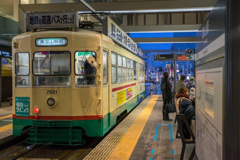 Mucha gente que usa la tranvía de Centram en la estación de Toyama en la noche fotos de archivo