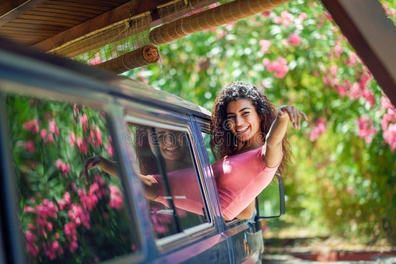 Muchacha árabe feliz que mira a escondidas hacia fuera la ventana de una furgoneta fotografía de archivo libre de regalías