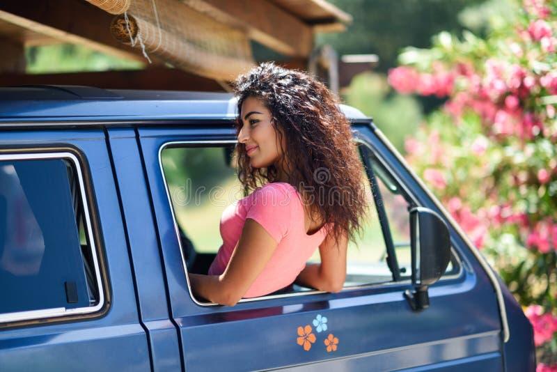 Muchacha árabe feliz que mira a escondidas hacia fuera la ventana de una furgoneta fotografía de archivo