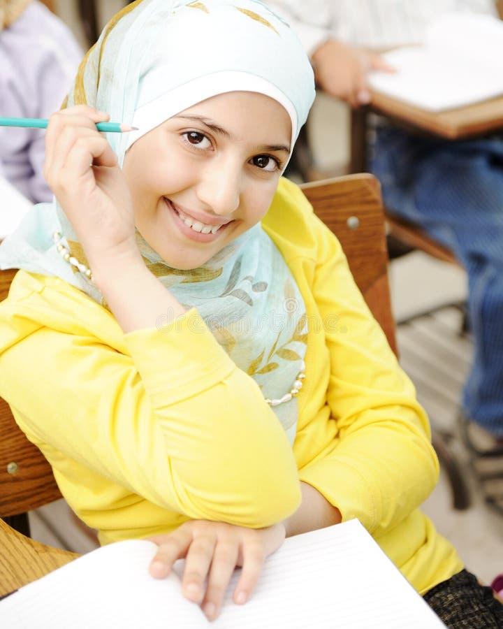 Muchacha árabe musulmán linda que se sienta en la silla foto de archivo