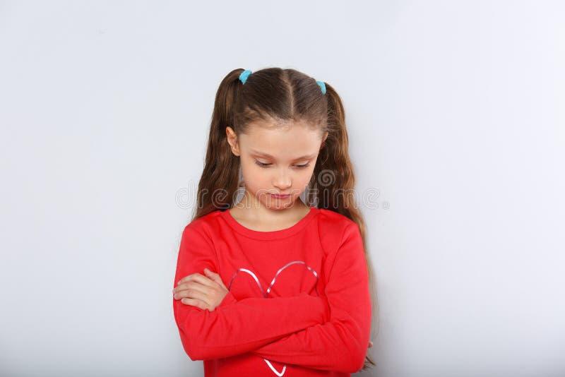 Muchacha abandonada triste del niño en la blusa roja de la Navidad que parece infeliz con los brazos doblados que miran abajo fotos de archivo