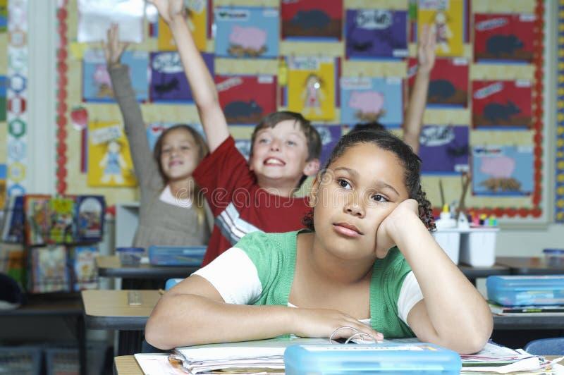 Muchacha aburrida con los compan@eros de clase que aumentan las manos en fondo fotografía de archivo