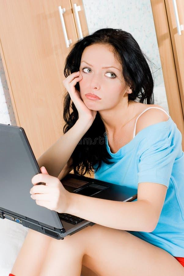 Muchacha aburrida con una computadora portátil foto de archivo libre de regalías