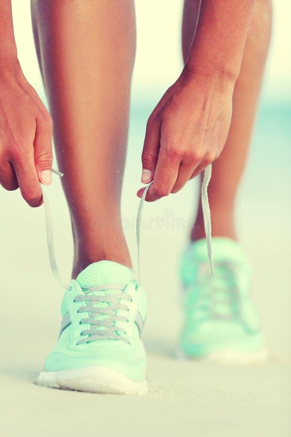 Muchacha activa del corredor de la vida que ata cordones de zapatillas deportivas fotos de archivo