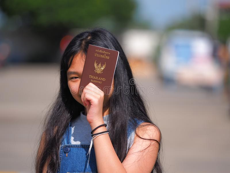 Muchacha adolescente asiática con el pelo negro largo que sostiene el pasaporte tailandés imagen de archivo