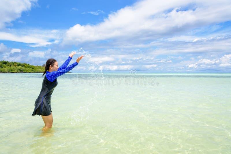 Muchacha adolescente asiática feliz jugar salpicar el agua en el mar imágenes de archivo libres de regalías