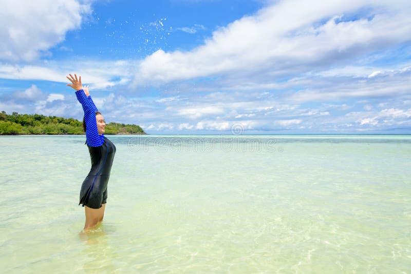Muchacha adolescente asi?tica feliz jugar salpicar el agua en el mar fotos de archivo