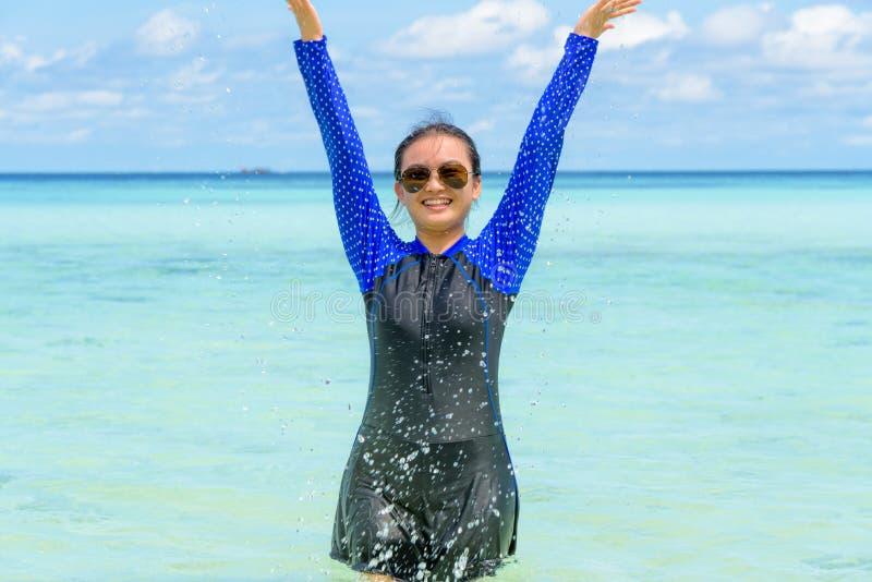 Muchacha adolescente asi?tica feliz jugar salpicar el agua en el mar imagen de archivo
