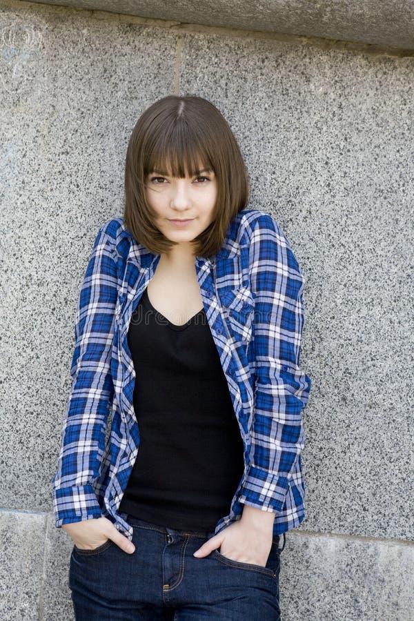 Muchacha adolescente atractiva seria en camisa marcada con cuadros foto de archivo