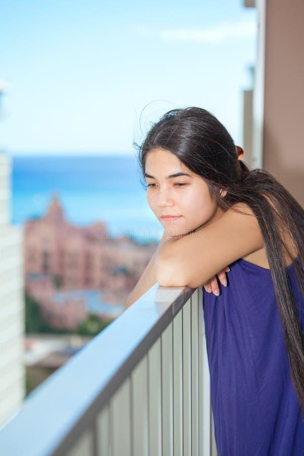 Muchacha adolescente biracial triste en el patio al aire libre del highrise, backgro del océano imagen de archivo libre de regalías
