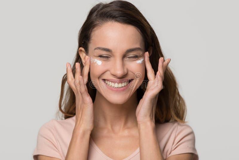 Muchacha adolescente bonita sonriente que aplica la crema cosmética hidratante en cara fotografía de archivo