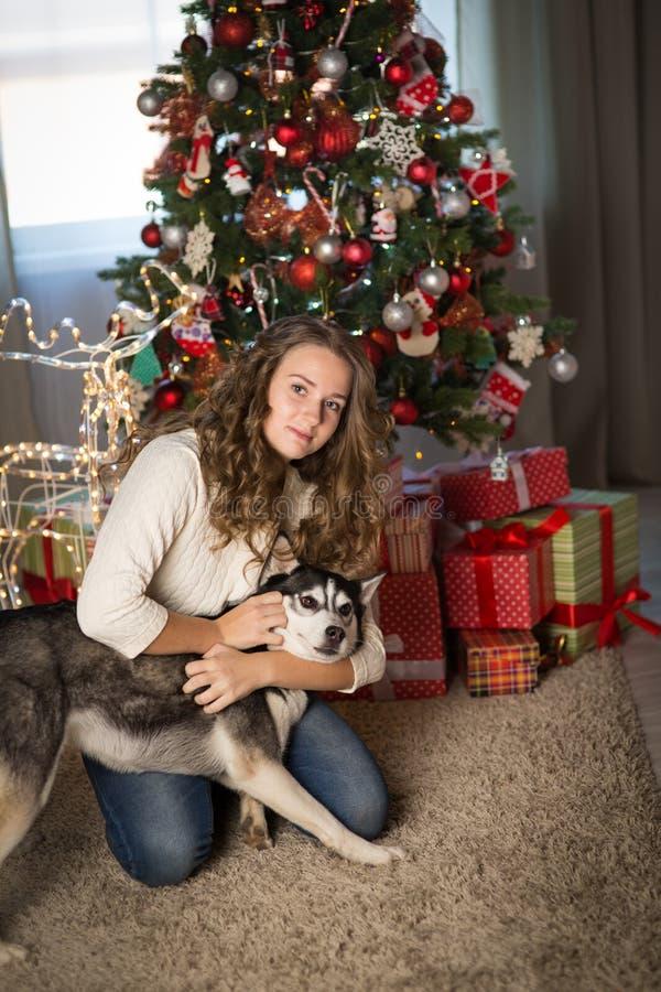 Muchacha adolescente con el perro, para la Navidad fotos de archivo