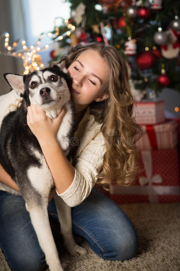 Muchacha adolescente con el perro, para la Navidad foto de archivo