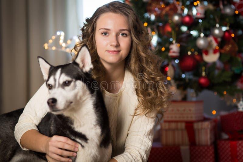 Muchacha adolescente con el perro, para la Navidad fotografía de archivo libre de regalías