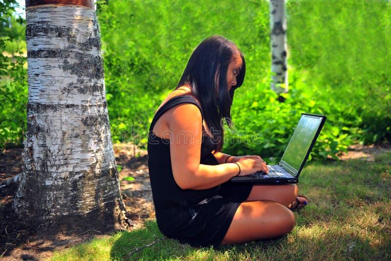 Muchacha adolescente con la computadora portátil fotografía de archivo libre de regalías