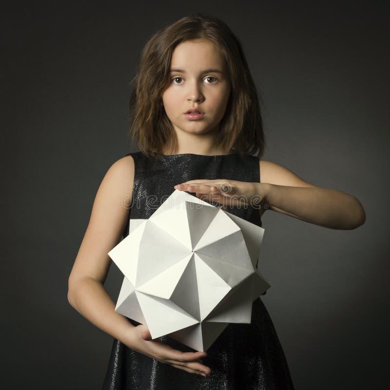 Muchacha adolescente con la figura del polígono del papel a disposición. imagen de archivo libre de regalías