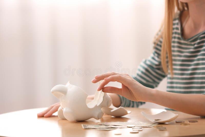 Muchacha adolescente con la hucha y el dinero quebrados en casa imagen de archivo
