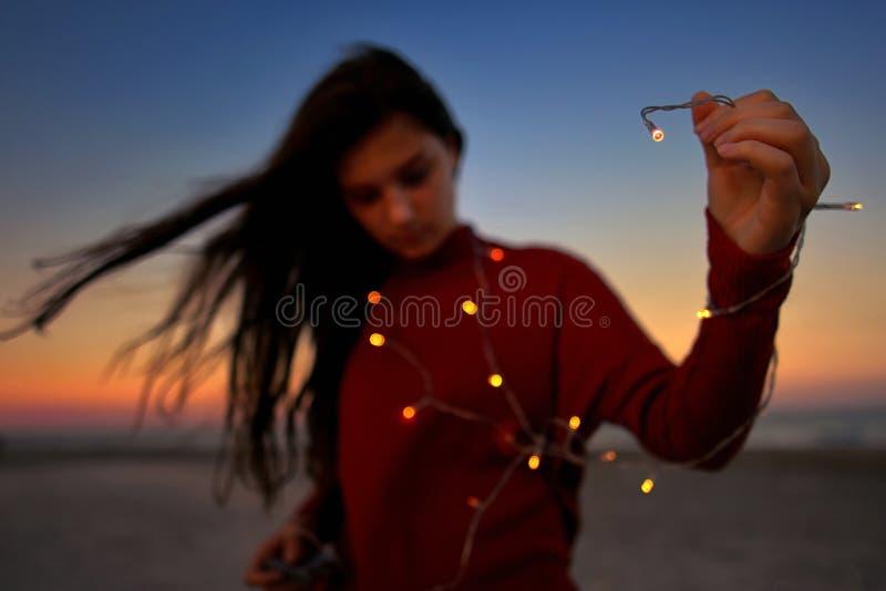 Muchacha adolescente con las luces en la playa fotos de archivo