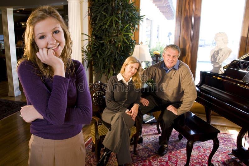 Muchacha adolescente con los padres por el piano fotografía de archivo libre de regalías