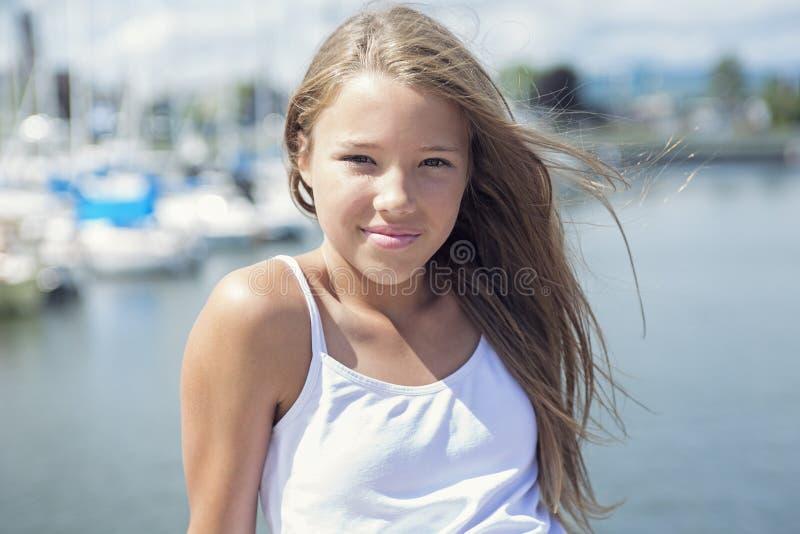 Muchacha adolescente de pelo largo joven que se coloca en la playa fotografía de archivo