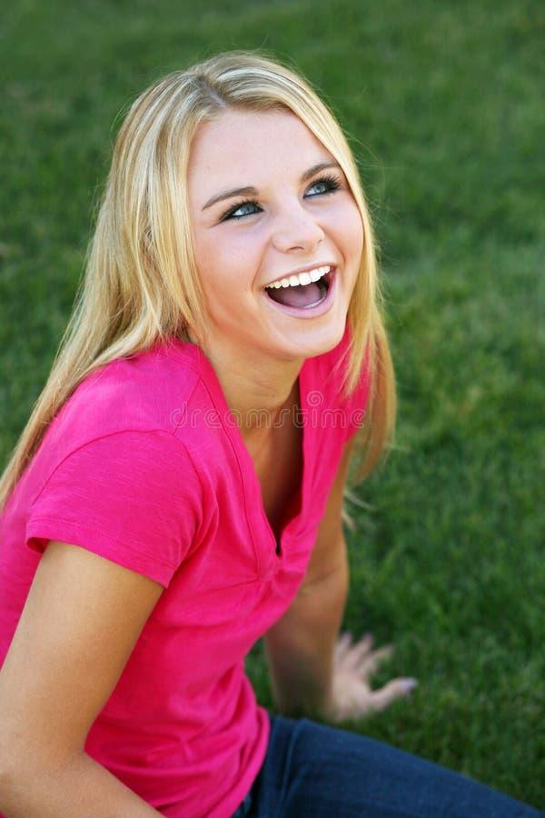Muchacha adolescente de risa en hierba imágenes de archivo libres de regalías