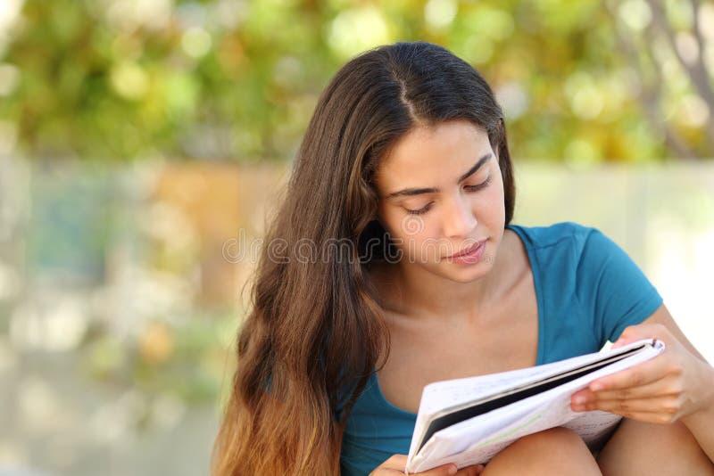 Muchacha adolescente del estudiante hermoso que estudia en un parque imagen de archivo