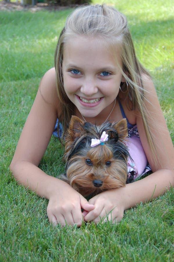 Muchacha adolescente del niño feliz que sonríe con el perrito del animal doméstico foto de archivo libre de regalías