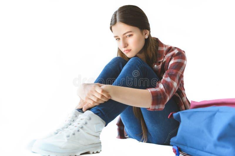 muchacha adolescente deprimida que se sienta cerca de la mochila solamente imagen de archivo libre de regalías