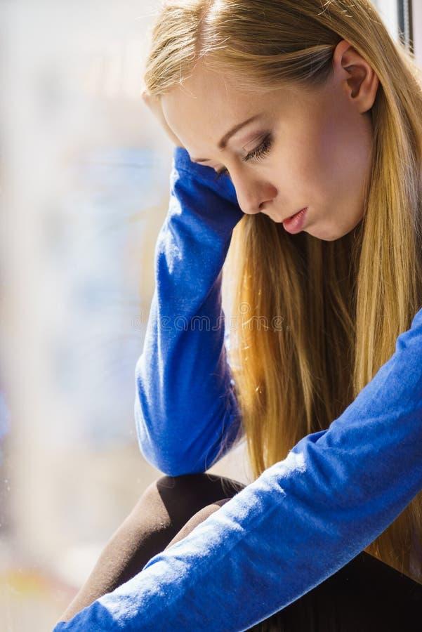 Muchacha adolescente deprimida triste que se sienta en travesaño de la ventana imagen de archivo