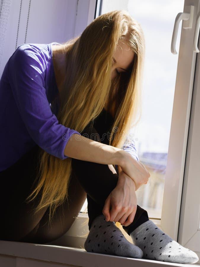 Muchacha adolescente deprimida triste que se sienta en travesa?o de la ventana fotos de archivo libres de regalías