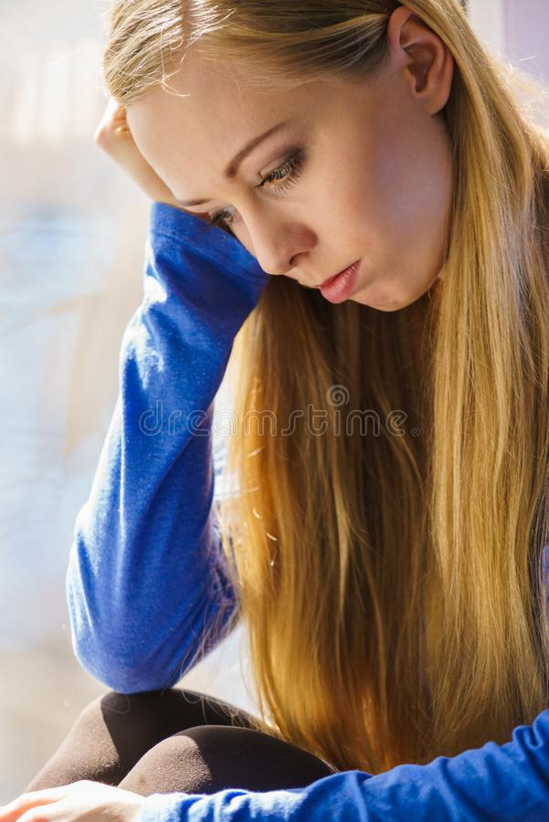 Muchacha adolescente deprimida triste que se sienta en travesa?o de la ventana fotos de archivo