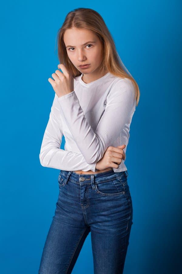 Muchacha adolescente elegante hermosa en fondo azul fotografía de archivo libre de regalías