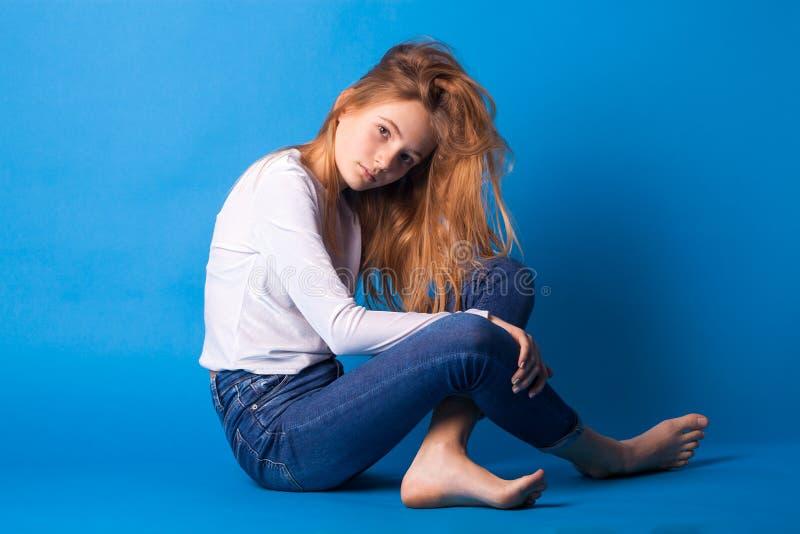 Muchacha adolescente elegante hermosa en fondo azul imagenes de archivo