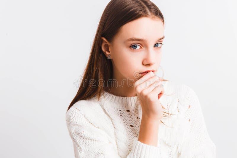 Muchacha adolescente emocional en un suéter hecho punto blanco en un fondo gris claro Espacio para el texto fotos de archivo libres de regalías