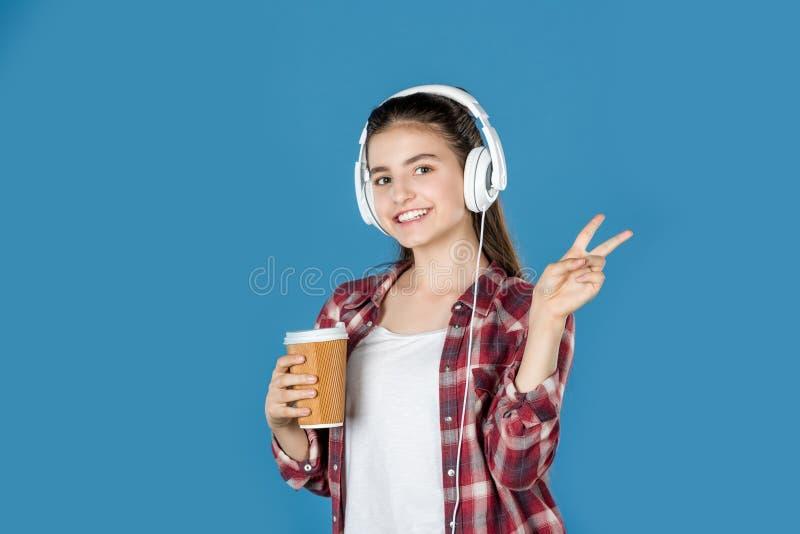 muchacha adolescente en auriculares con el café que muestra el signo de la paz foto de archivo