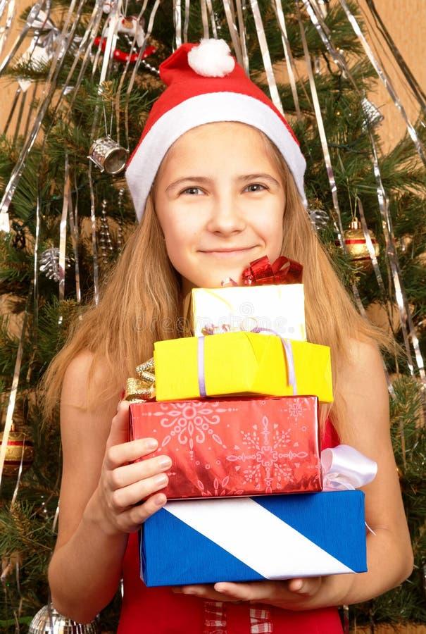 Muchacha adolescente en el casquillo de la Navidad que sostiene los regalos foto de archivo