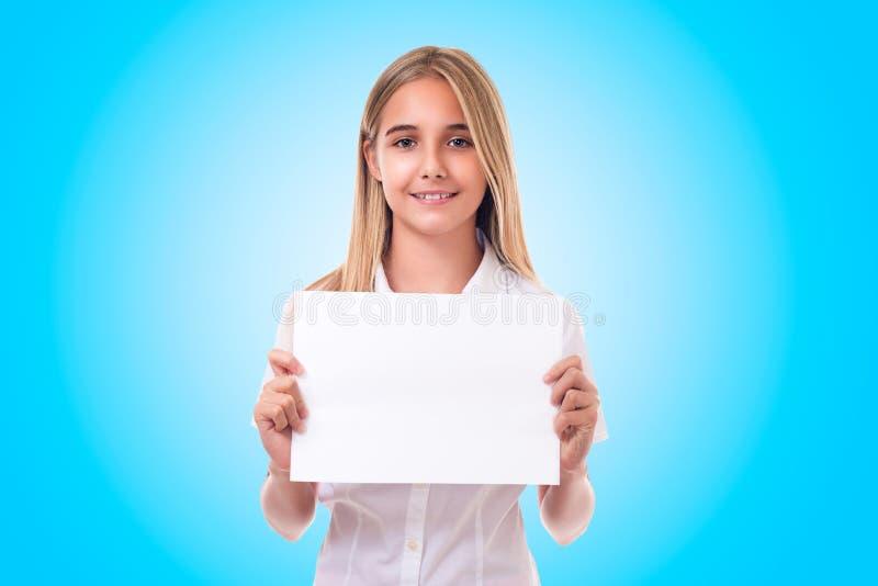 Muchacha adolescente en el tablero blanco de la muestra de publicidad de la tenencia de la camisa , aislado imagen de archivo libre de regalías