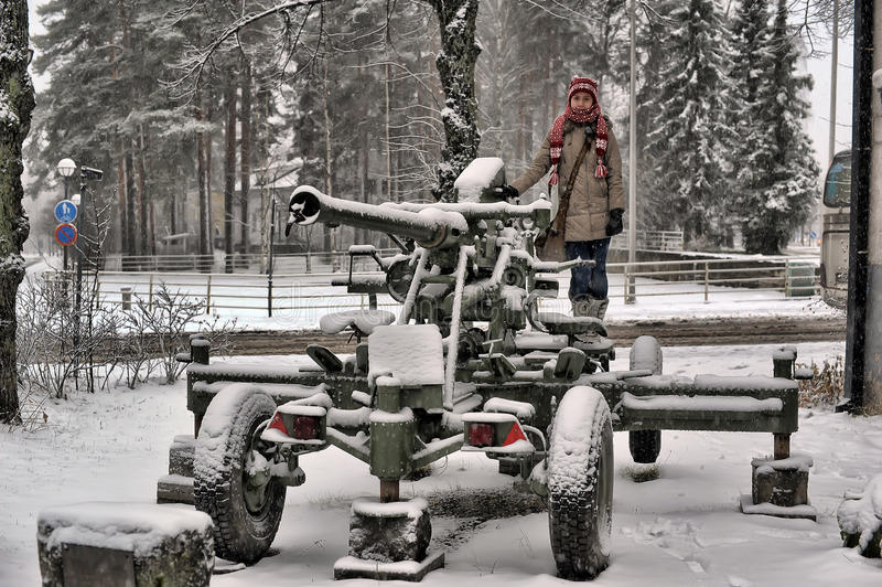 Muchacha adolescente en invierno cerca del cañón viejo de la Segunda Guerra Mundial fotografía de archivo