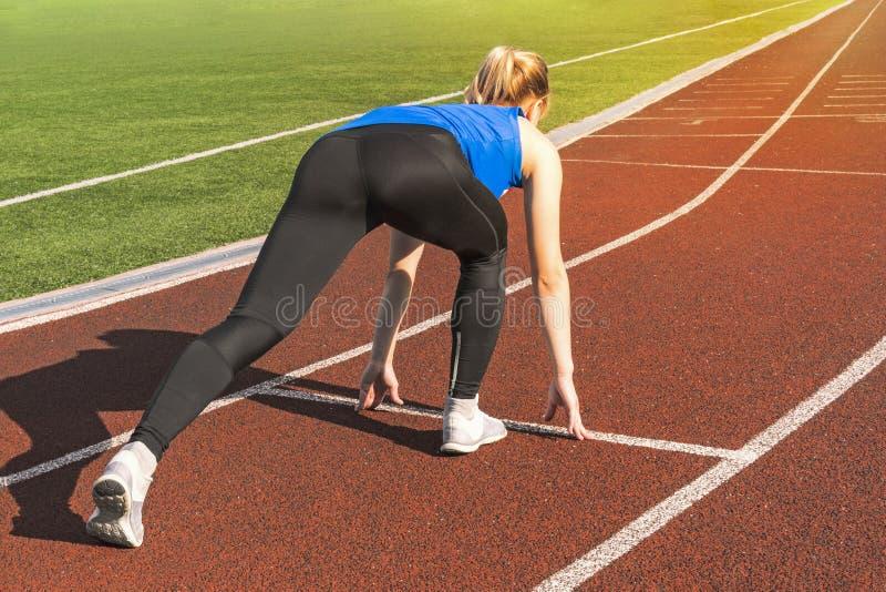 Muchacha adolescente en los bloques el comenzar en una reunión de pista Comienzo de los deportes muchacha en actitud en la línea  foto de archivo