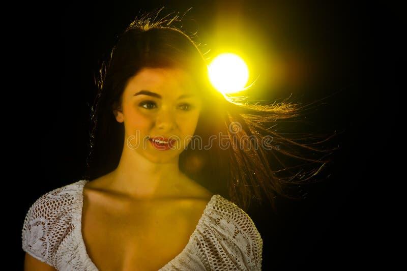 Muchacha adolescente en un resplandor amarillo. imagen de archivo