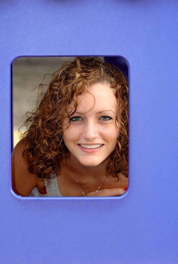 Muchacha adolescente en ventana azul foto de archivo