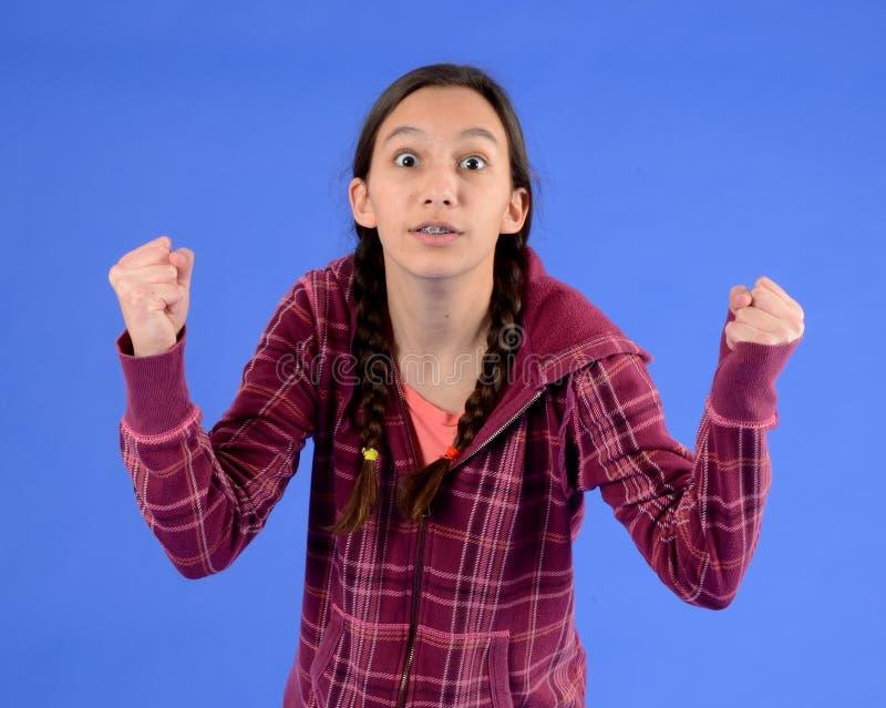Muchacha adolescente enojada con las trenzas con los puños para arriba imagenes de archivo