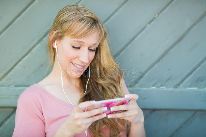 Muchacha adolescente feliz que escucha la música en su teléfono elegante imágenes de archivo libres de regalías