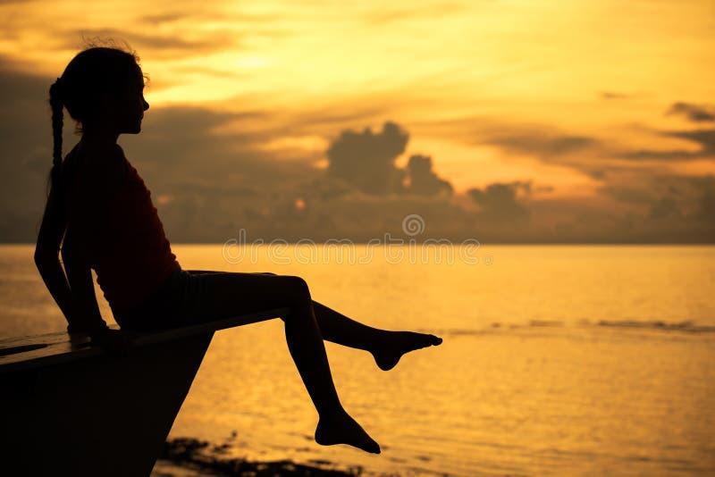 Muchacha adolescente feliz que se sienta en la playa fotografía de archivo