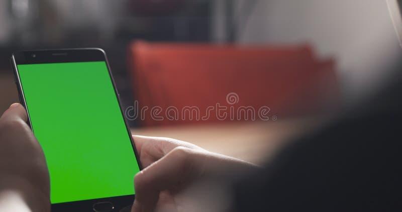 Muchacha adolescente femenina que usa smartphone con la pantalla verde que se sienta en la tabla foto de archivo libre de regalías