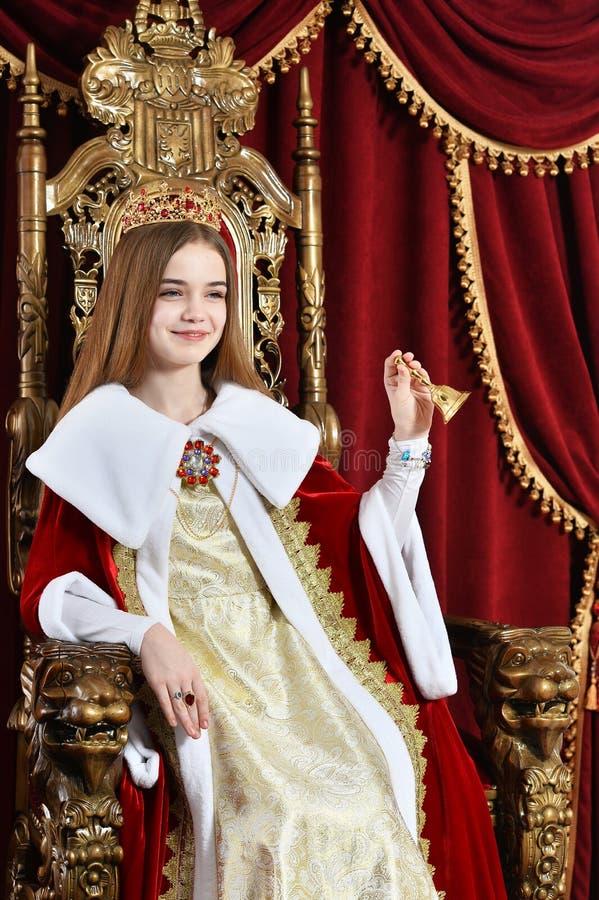 Muchacha adolescente hermosa con la corona que sostiene la campana de mano mientras que sienta i imagen de archivo