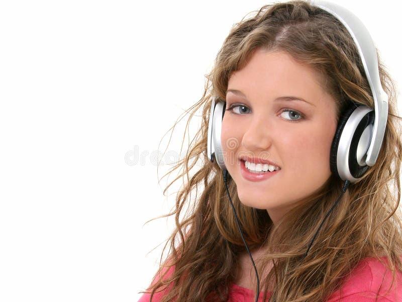 Muchacha adolescente hermosa con los auriculares imagen de archivo